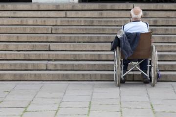 Alter Mann steht mit einem Rollstuhl vor einer Treppe und benoetigt Hilfe.