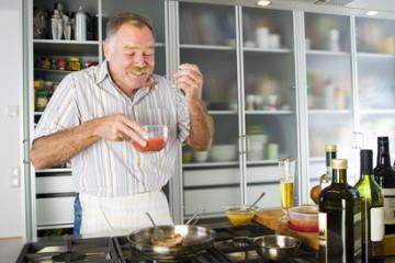Ein älterer Herr kocht in einer barrierefreien Küchen