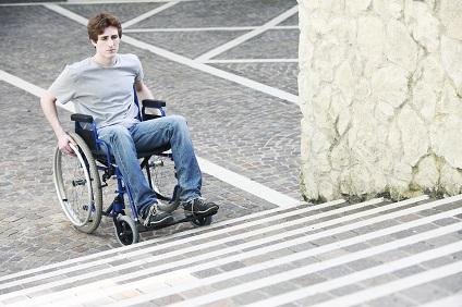 Junger Rollstuhlfahrer vor Treppen