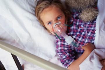 Kind im Bett mit Sauerstoff-Maske